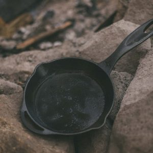 "8"" Cast Iron Camping Pan on stones"