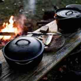 Large Camping Crock Pot next to Dutch Oven