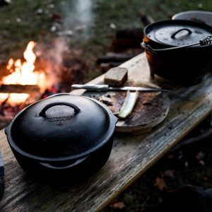Large Camping Crock Pot next to Dutch Oven