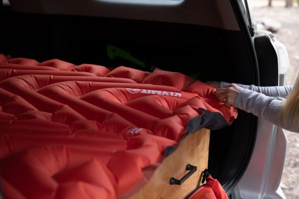 Double Sleeping Pad being inflated in back of car