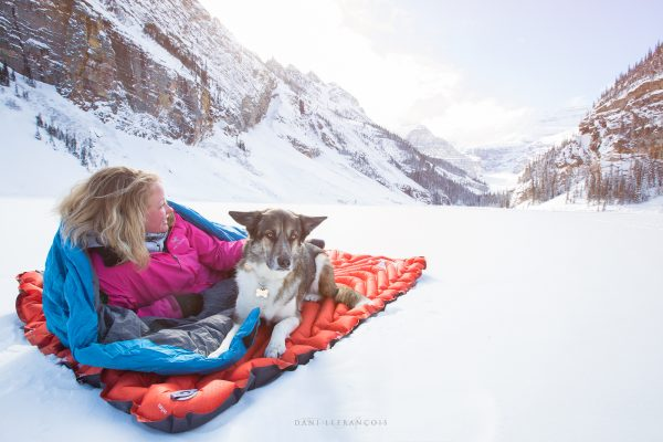 Double Sleeping Pad being used by woman and dog on snow